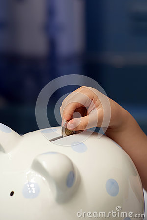 Child putting a coin into piggy bank