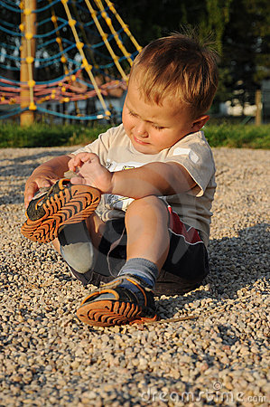 Free Child Putting His Shoes On Stock Photo - 19919190