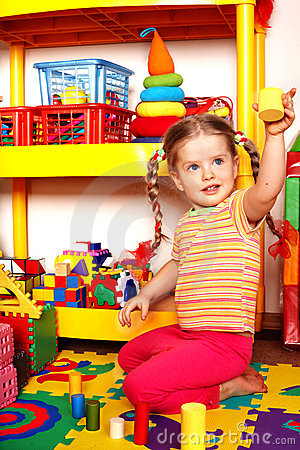 Child with puzzle and wood block  in play room.