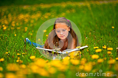 Child reading a book while lying
