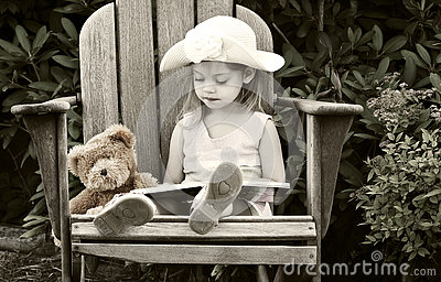 Child reading to her teddy bear