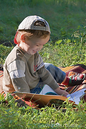 Child reads book and smiles