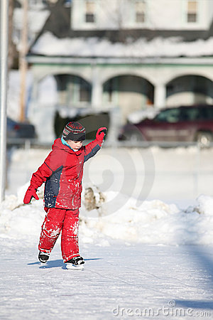 Child in red ice skating in public park