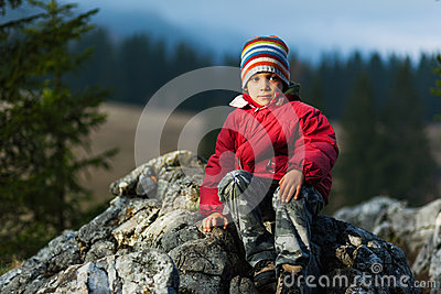 Child resting on cliff