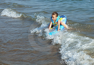 Child rides a wave of the sea.