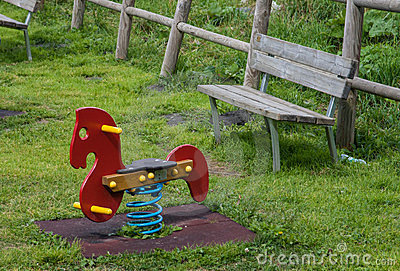 Child riding rocking horse in playground