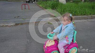 Child riding a toy car in the park stock footage