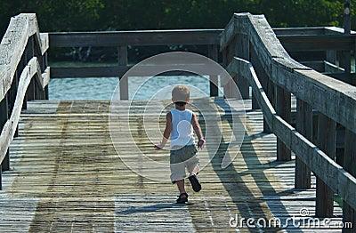 Child running on pier