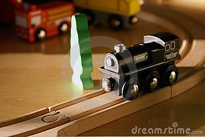 Child s black wooden toy train on wood tracks