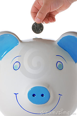Child s hand dropping a quarter in piggy bank