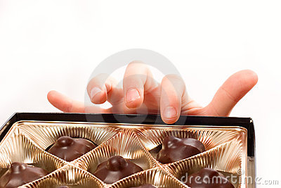 Child s hand picking chocolate candy from box isol