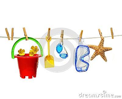 Child s summer toys on clothesline against white