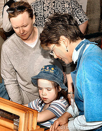 Child s weaving lesson at fair Editorial Stock Image