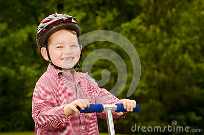 Child with safety helmet riding scooter