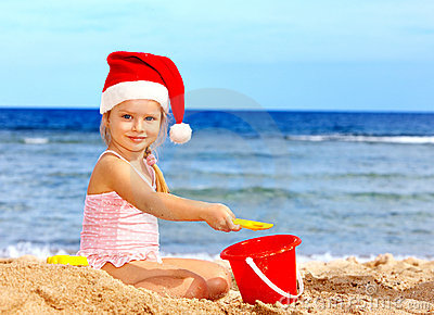 Child in santa hat playing on  beach.