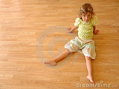 Child sits on wooden floor