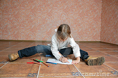 Child sitting on the floor and drawing