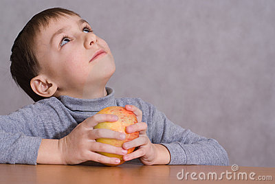 Child sitting next to an apple and dreams