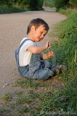 Child sitting by the roadside
