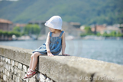 Child sitting on a stone parapet