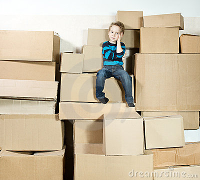Child sitting on top of heap carton boxes.