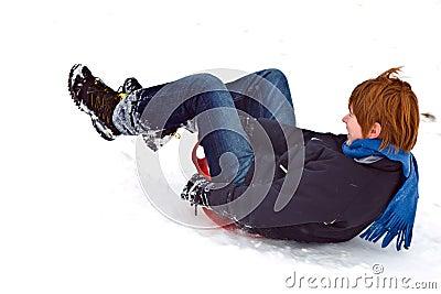 Child sledding down the hill in snow, white winter