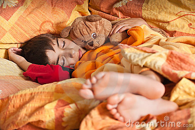 Child sleep in bed bare feet