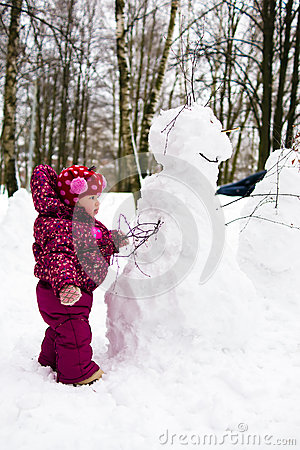 Child with snowman in winter park