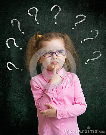 Child standing near school chalkboard with many question marks