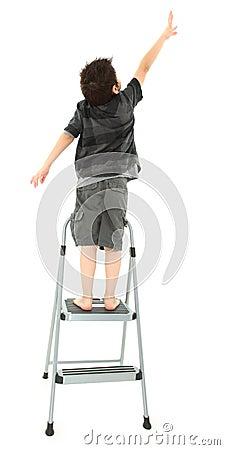 Child on Step Ladder Reaching Up
