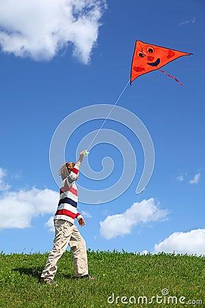 Child in summer starts air serpent in blue sky