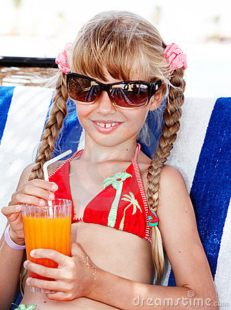 Child  in sunglasses and red bikini drink  juice.