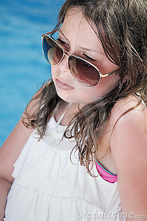 Child in Sunglasses Sitting Next to the Pool