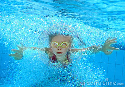 Child  swim underwater in pool.