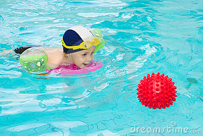 Child swimming pool, kid playing water ball, boy indoor training