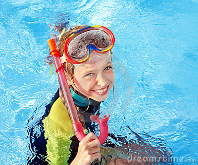 Child in swimming pool learning snorkeling.