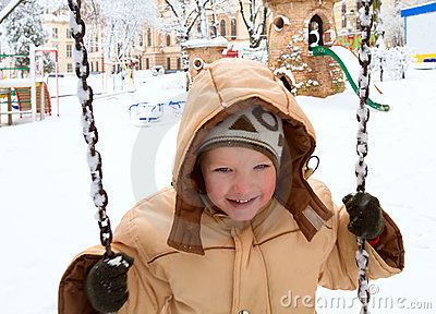 Child on swing in winter park