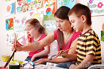 Child with teacher draw paints in play room.