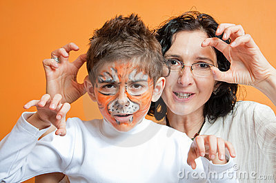 Child in tiger make-up and mother roaring