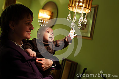 Child touching chandelier