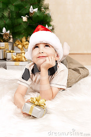 Child under the Christmas tree with gifts