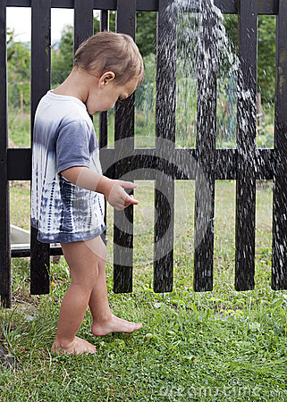 Child under garden water shower
