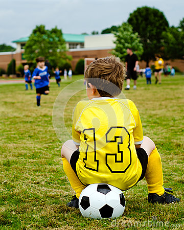 Child in uniform watching soccer game