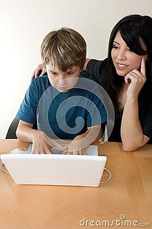 Child using laptop while adult supervises