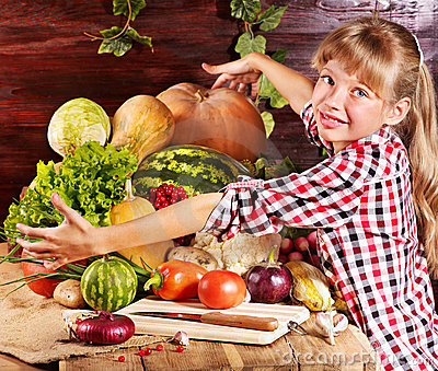 Child with vegetable on kitchen.