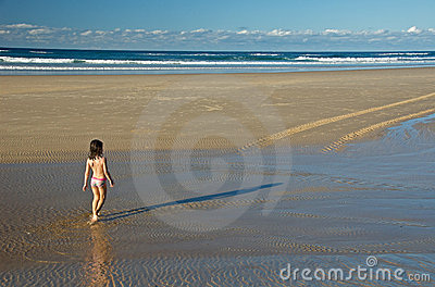 Child walking towards ocean