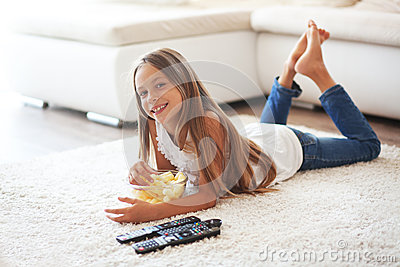 Old Child Watching Tv Laying Down On A White Carpet At Home Alone