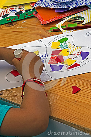 Child Which Sticks Together Pieces Of Colored Paper Stock ...