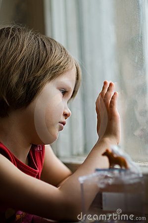 Child at the window on a rainy day