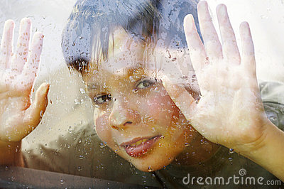 Child and window on a wet rainy day